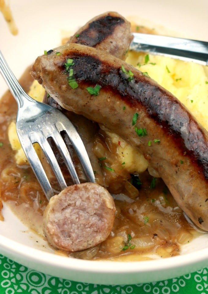 A white bowl containing yukon Gold Mashed potatoes, onion ale gravy, and two sausages (bangers). A sausage is cut open revealing the inside