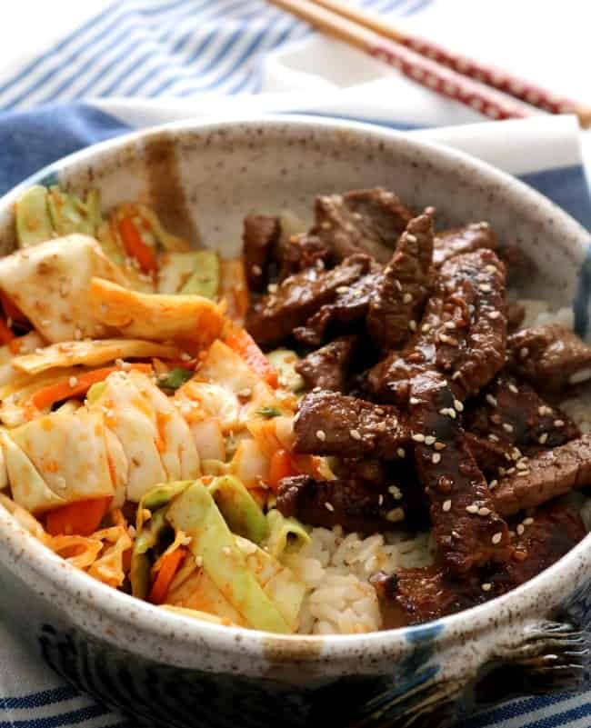 A bowl of Spicy Korean Bulgogi Beef - Ready in minutes, these Spicy Korean Bulgogi Beef Bowls are budget-friendly and seriously delicious. Serve with my quick Kimchi and steamed rice for a quick and easy weeknight meal! #GlobalStreetFood #Beef #KitchenDreaming #Bulgogi #Korean #Kimchi #Rice #Asian #Recipe