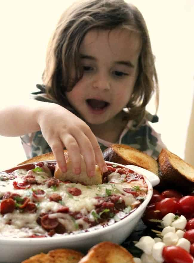 a child is pictured digging into the pizza dip with a piece of toasted bread.