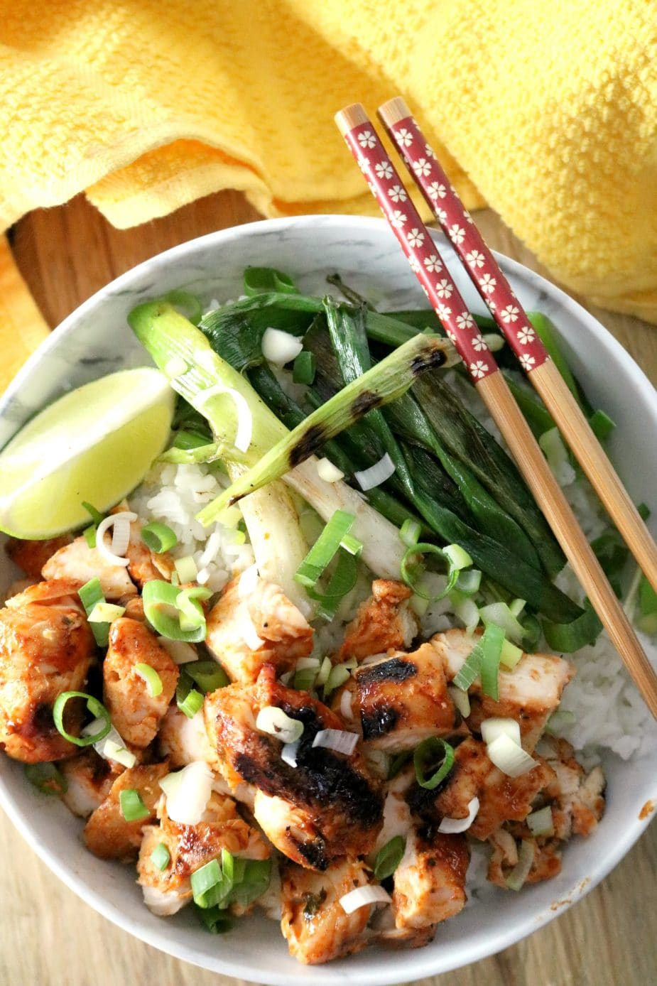 Grilled Korean Chicken skewers in a bowl on a bed of rice with a side of grilled green onions and a wedge of lime for garnish.
