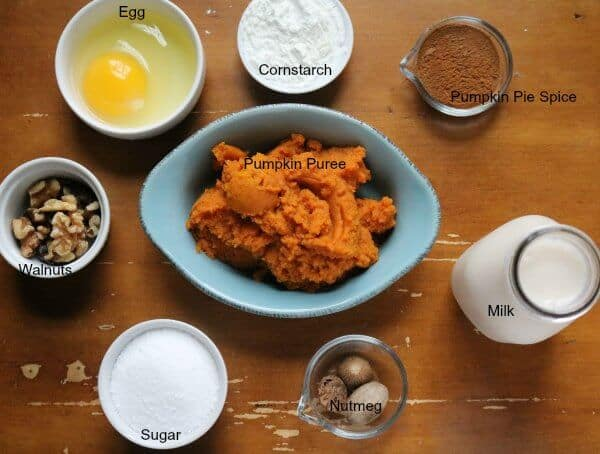 The ingredients for pumpkin pie pudding placed out on a brown table; pumpkin puree, egg, cornstarch, pumpking pie spice, walnuts, milk, sugar, nutmeg, salt, and vanilla.