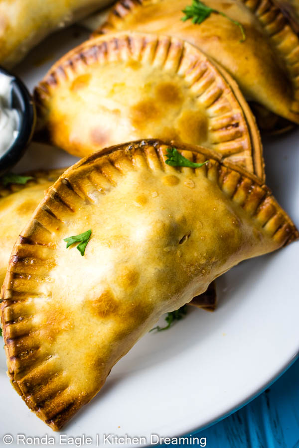 a close up photo of a plate of baked empanadas. You can see the pattern on the edge where it has been crimped with a fork. The empanadas have a varied coloration of golden yellow to golden brown from the way the egg wash cooked in the oven.