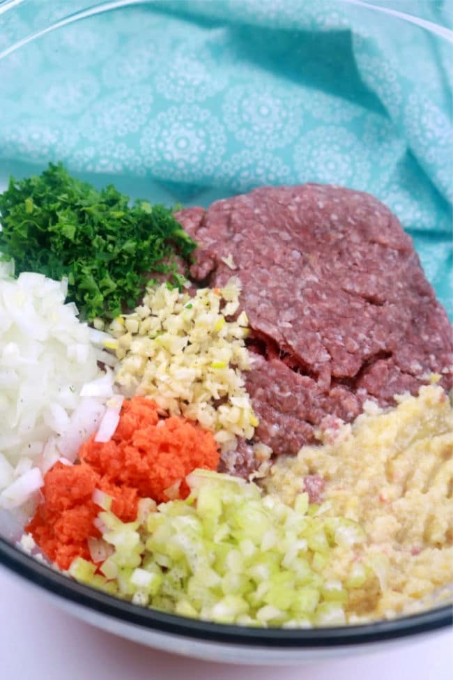 A large mixing bowl with the ingredients for meatloaf: minced beef, chopped parsley, minced garlic, diced onions, grated carrot, diced celery, breadcrumbs, milk, egg. salt. and pepper.