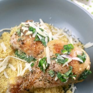Baked Garlic Parmesan Chicken Plated in a shallow bowl over couscous with parmesan cheese 1