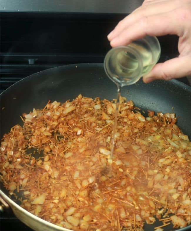 Wine being poured into the toasted rice to deglaze the pan.