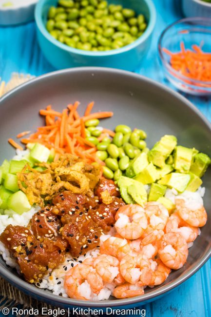 A bowl of shrimp poke with avocado, edamame, seaweed salad, shredded carrots, cucumbers, crispy fried onions, and a drizzle of sriracha sauce.