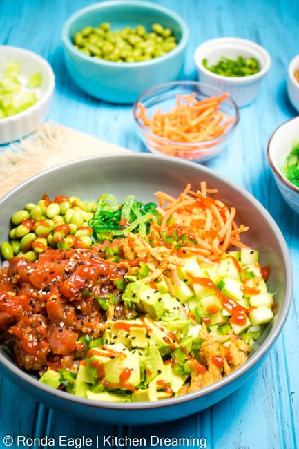 A 3/4 photo of a bowl of tuna poke with avocado, edamame, seaweed salad, shredded carrots, cucumbers, jalapenos and a drizzle of sriracha sauce.