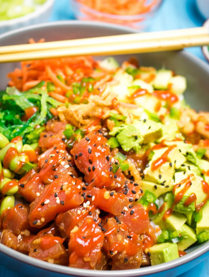 A bowl of tuna poke with avocado, edamame, seaweed salad, shredded carrots, cucumbers, jalapenos and a drizzle of sriracha sauce.