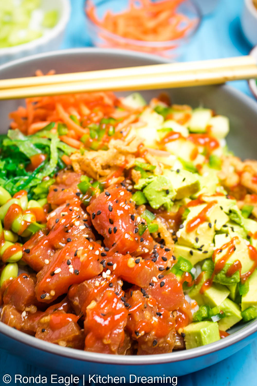 A bowl of tuna poke with avocado, edamame, seaweed salad, shredded carrots, cucumbers, jalapenos and a drizzle of sriracha sauce.