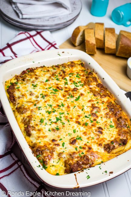 In image of a baked spaghetti casserole in a baking pan with slices of garlic bread and butter on a cutting board.