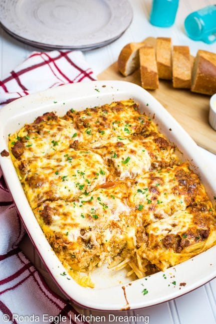 In image of a baked spaghetti casserole in a baking pan with slices of garlic bread and butter on a cutting board. A slice has been removed from the lower left corner of the pan.
