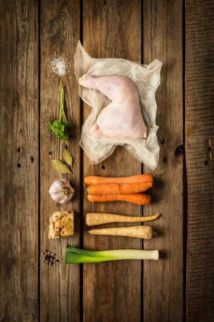 The ingredients for chicken stock laid out on a rustic brown wooden table. The ingredients include chicken legs (and thighs), salt, black pepper, parsley, bay leaves, garlic, carrots. and green onions.