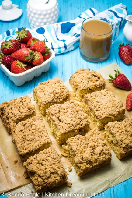 Coffee cake squares on a piece of parchment paper. They have been spaced apart to see the moist and tender texture of the cake.