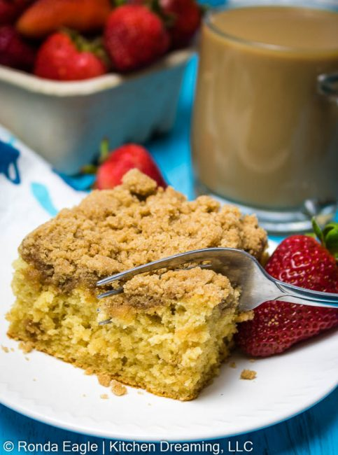 a close-up image of a slice of gluten0free coffee cake on a plate. from the screen, a fork is seen cutting a slice out of the cake to be eaten. In the background is a cup of coffee