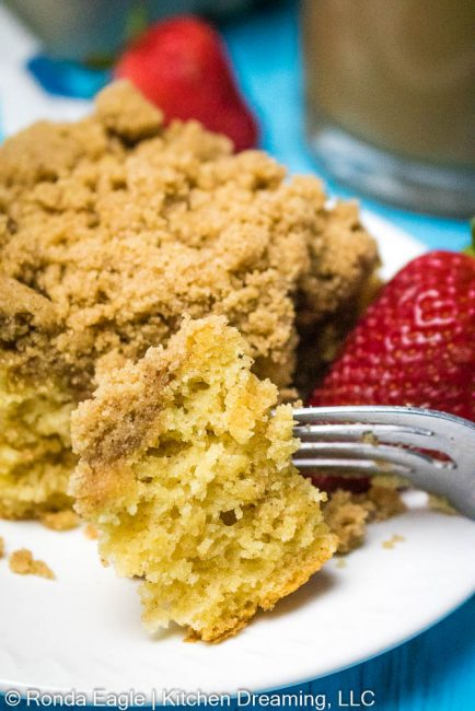 An up-close image of the tender and moist crumb of the gluten-free coffee cake. A fork rests on the edge of the white serving plate. Red berries can be seen in the background.