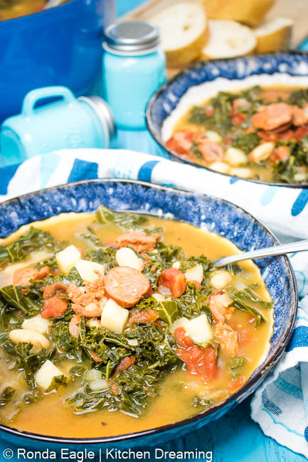 A blue bowl filled with Portuguese Sausage and Kale Soup, a spoon handle sticks out of the right side of the bowl. Looking inside you can see bright green kale, diced white potatoes, white kidney beans, sausage rounds, diced tomatoes, and onions in a rich stock.