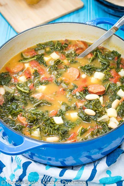 A large pot of Portuguese Sausage and Kale Soup with a ladle sticking out of the top of the pot. Looking inside you can see bright green kale, diced white potatoes, white kidney beans, sausage rounds, diced tomatoes, and onions in a rich stock.