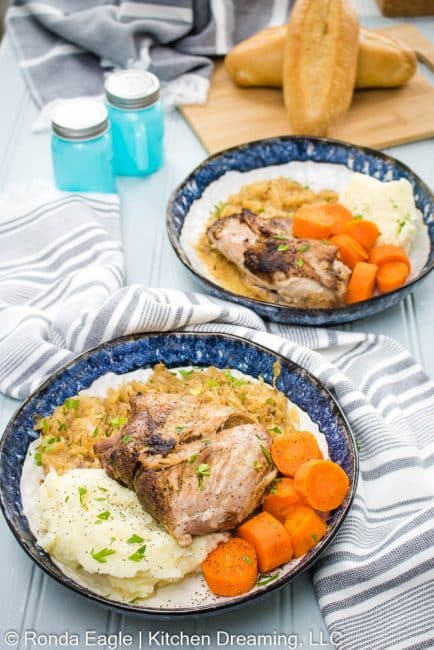A bowl of braised pork with sauerkraut and glazed carrots.