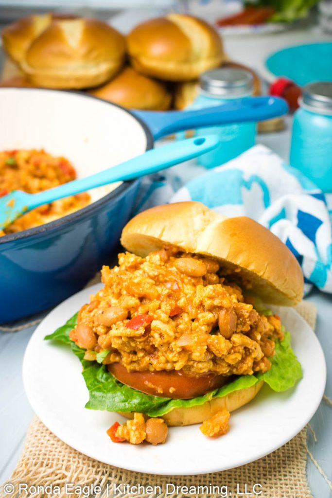 An image of a sloppy joe sandwich on a white plate. The bun is tilted back off the sandwich revealing the chicken sloppy joe underneath. There's a pan of sloppy joe mix in the background.