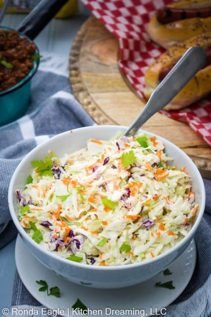 A large bowl of homemade coleslaw on a table. Grille hot dogs and a pot of hot dog (chili)  sauce are in the background.