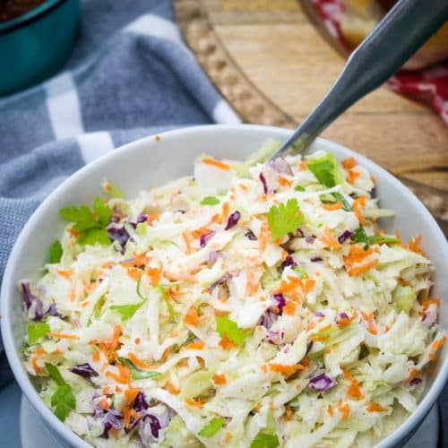An image of a bowl of coleslaw on a picnic table.