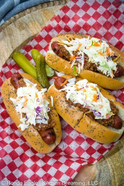 A plate with three grilled hotdogs topped with hot dog chili sauce and creamy homemade coleslaw.