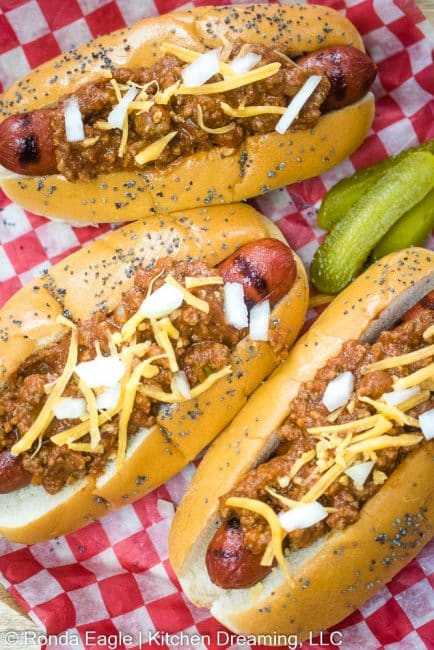An over head shot of grilled chili dogs topped with hot dog chili, onions, and shredded cheddar cheese.
