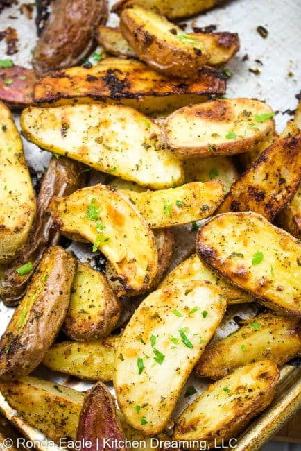 roasted parmesan ranch potato wedges on a sheet pan ready to be served.