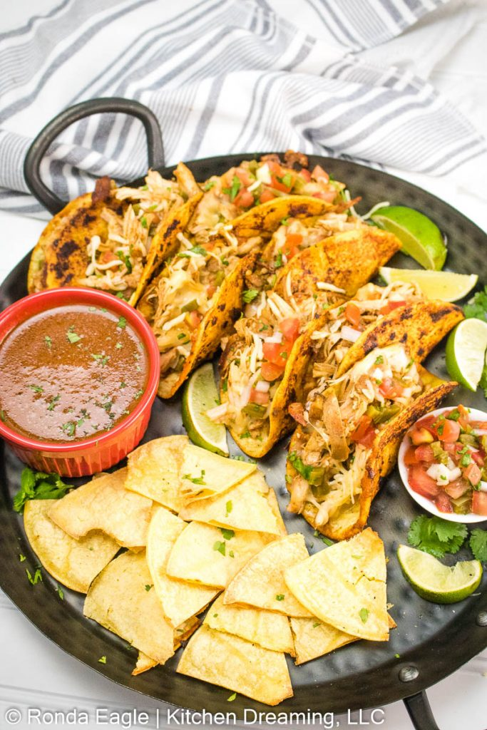 A tray of chicken Birria tacos with a side of air fryer corn tortilla chips. A bowl of adobo consomé and pico de gallo con nopalitas is on the tray with wedges of lime for serving.