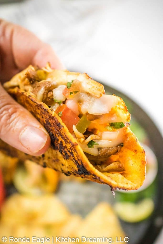 A hand is holding an assembled taco at the ready - waiting to take the first highly anticipated bite.