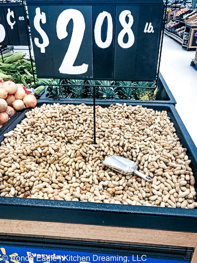 An image of a large barrel of green peanuts at the grocery store.