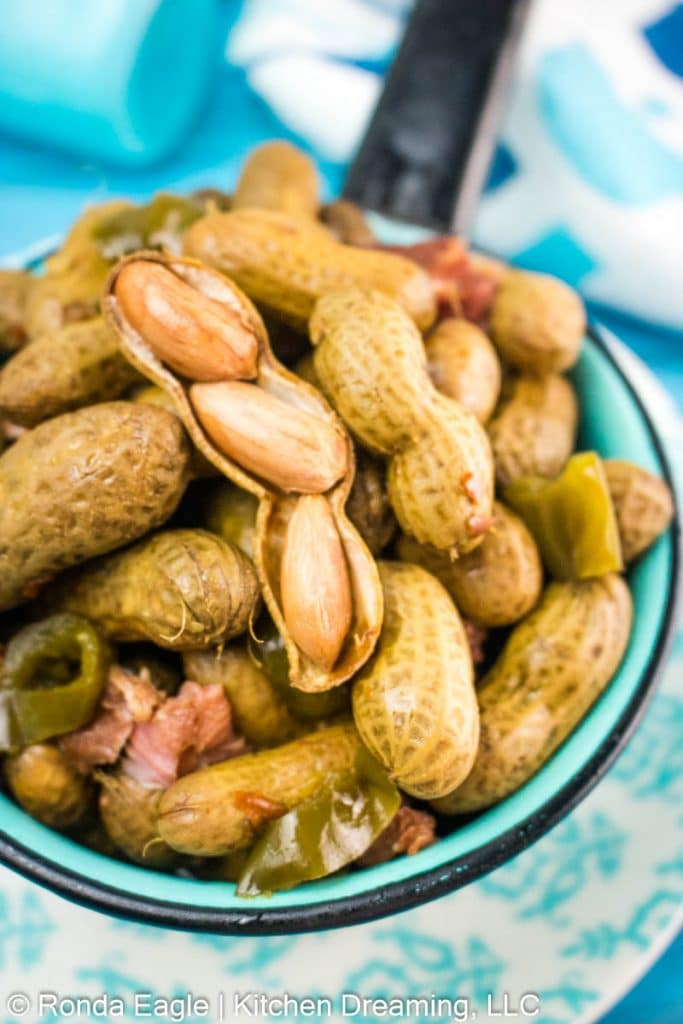 A small blue pot filled with Crock Pot Cajun boiled peanuts. Bits of smoked ham and jalapeno peppers are seen amidst the boiled peanuts. One shell is broken open to show the soft yet slightly crunchy texture of the peanuts.